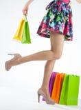 女性腿和多彩多姿的购物袋 免版税图库摄影