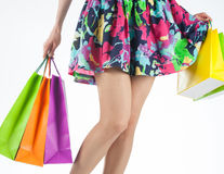 女性腿和多彩多姿的购物袋 免版税库存图片