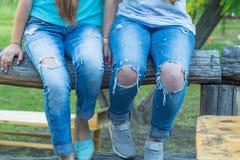 女性腿和膝盖在被撕毁的牛仔裤 女孩的时兴的牛仔布衣物 有孔的,行家,街道时尚裤子 图库摄影