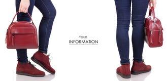 女性腿在牛仔裤和在有红色皮包提包时尚美容院购买集合样式的红色绒面革鞋子 库存照片