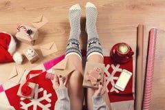 女性腿特写镜头在温暖的袜子的与鹿、圣诞节礼物、包装纸、装饰和杯子热奶咖啡顶视图 图库摄影
