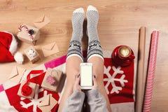 女性腿特写镜头在温暖的袜子的与鹿、圣诞节礼物、包装纸、装饰和杯子热奶咖啡顶视图 库存照片