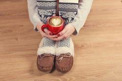 女性腿特写镜头在温暖的袜子的与鹿、圣诞节礼物、包装纸、装饰和杯子热奶咖啡顶视图 库存图片