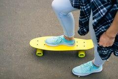 女性腿顶视图在牛仔裤和运动鞋的在黄色skateboa 免版税图库摄影