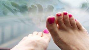 女性腿,修脚特写镜头有明亮的指甲的 在挡风玻璃前面的谎言 它下雨的` s,汽车刮水器是 影视素材