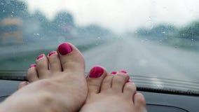 女性腿,修脚特写镜头有明亮的指甲的 在挡风玻璃前面的谎言 它下雨的` s,汽车刮水器是 股票录像