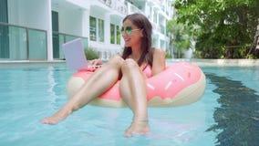 女性自由职业者在水池的一个可膨胀的圈子坐并且投下膝上型计算机入水 繁忙在假日期间 股票视频