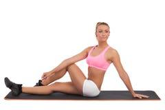 女性舒展在有氧席子在健身前 图库摄影