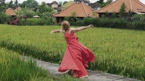 女性舞蹈家穿一件长的红色礼服,她的金发开花,并且她的嘴唇绘与明亮的唇膏,她 股票视频
