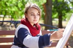 女性艺术家在秋天公园绘一幅画 库存图片