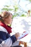 女性艺术家在秋天公园绘一幅画 免版税图库摄影