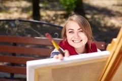 女性艺术家在秋天公园绘一幅画 免版税库存图片