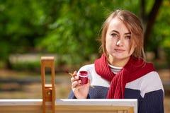 女性艺术家绘秋天风景的画 免版税库存照片
