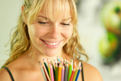 年轻女性艺术家藏品上色了铅笔和微笑 库存照片