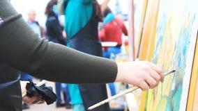 女性艺术家绘在夏天节日的一幅五颜六色的画 拥挤和被弄脏的背景的另一位艺术家 股票视频
