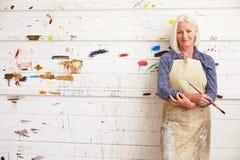 女性艺术家画象反对油漆的盖了墙壁 免版税图库摄影