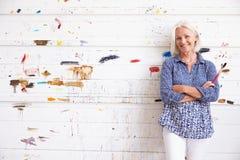 女性艺术家画象反对油漆的盖了墙壁 免版税库存图片