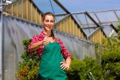女性花匠在商品菜园或苗圃里 免版税库存图片