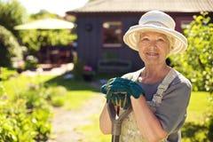 女性花匠画象在庭院里 图库摄影