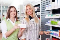 女性药剂师劝告顾客在药房 免版税库存照片
