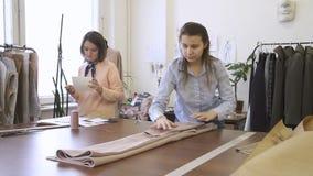 女性衣物设计师放置衣裳,站立在桌上,同事做笔记,妇女  股票视频