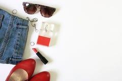 女性衣裳平展放置与化妆用品和辅助部件在白色背景 免版税库存照片