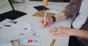 女性衣裳设计师的手画的剪影特写镜头在纸的在桌上 影视素材