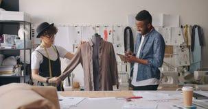 女性裁缝测量的服装,当在笔记本谈的微笑时的人文字 股票视频