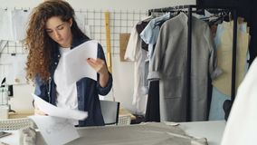 女性裁缝铺开在然后采取服装剪影和画在纸的演播室桌上的织品螺栓 设计 股票录像