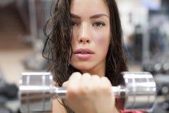 年轻女性解决与在健身房的哑铃 库存照片
