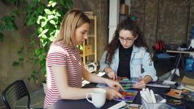 女性设计师与色板显示一起使用确定在照片的颜色 他们庆祝成功与 股票视频