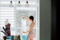 女性设计师与被编织的礼服一起使用在内部舒适的演播室,自由职业者,生活方式,启发概念 库存图片