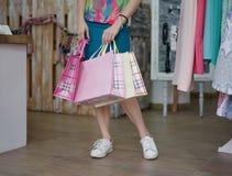 女性购买礼物的特写镜头 拿着与衣裳的女售货员袋子在商店背景 消费者至上主义概念 库存图片