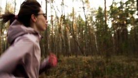女性赛跑在有高楼的小郊区镇在背景中 金黄日出,慢动作 股票视频