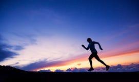女性赛跑者剪影,遇到日落 免版税库存图片