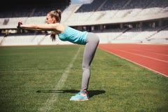 女性赛跑者舒展,为训练做准备 做准备为跑的健身女运动员在轨道 库存照片
