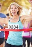 女性赛跑者赢取的马拉松 图库摄影