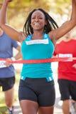 女性赛跑者赢取的马拉松 免版税库存照片
