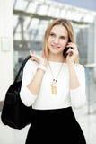 年轻女性走在打电话的时兴的成套装备在机动性 免版税库存照片