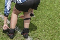 女性足球运动员去除她的攀蹬护卫 免版税库存图片