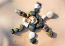 女性身体,太阳标志由白色小卵石石头做成 免版税库存图片