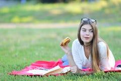 女性运作的在公园和食物快餐的玻璃 免版税库存图片