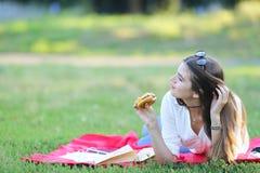 女性运作的在公园和食物快餐的玻璃 库存照片