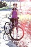女性运动佩带的自行车盔甲 免版税库存照片