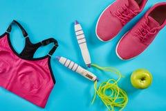 女性运动器材平的位置在桃红色颜色的与跳绳和运动鞋在蓝色背景 免版税库存照片