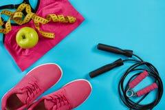 女性运动器材平的位置在桃红色颜色的与跳绳和运动鞋在蓝色背景 库存图片