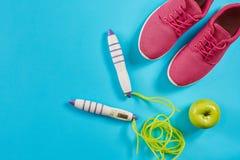 女性运动器材平的位置在桃红色颜色的与跳绳和运动鞋在蓝色背景 免版税库存图片