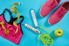 女性运动器材平的位置在桃红色颜色的与跳绳和运动鞋在蓝色背景 图库摄影