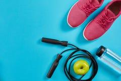 女性运动器材平的位置,跳绳、瓶水和在蓝色背景的桃红色运动鞋 图库摄影