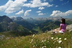 女性远足者享受从一个高山草甸的看法在高海拔 免版税库存图片